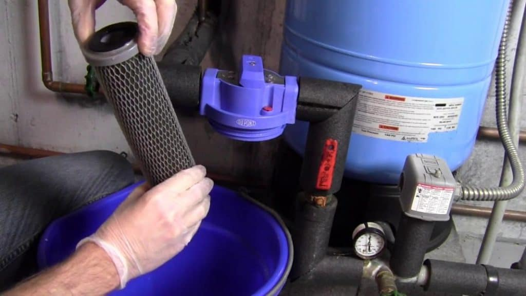 Picture of a person replacing filter cartridge of a whole house water filter system