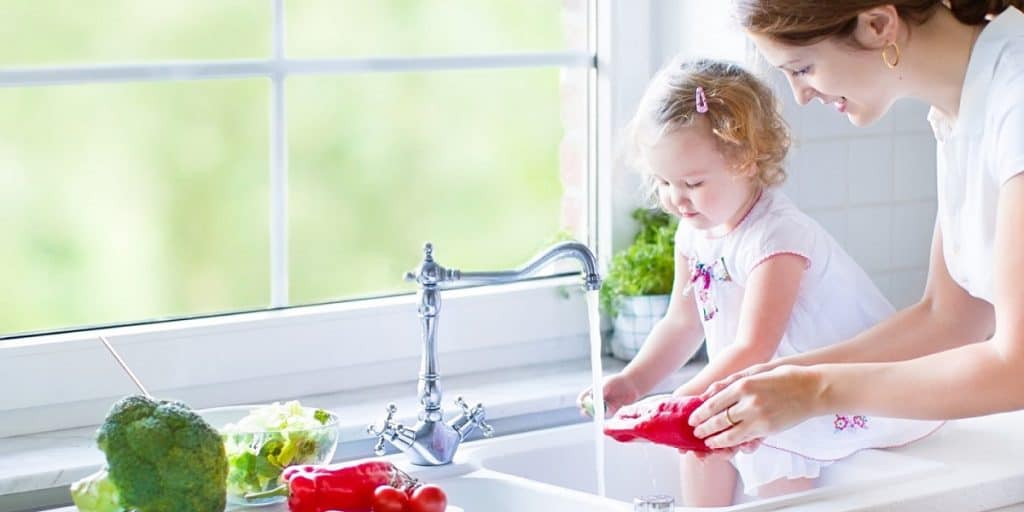 Picture of a mother and toddler using the sink to wash vegetables